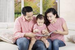 Ouders die verhaal op boek vertellen stock afbeeldingen