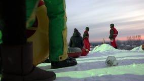 Ouders en gespecialiseerd personeel dat op kaastaartenkinderen worden gerold met sneeuw hallo stock footage