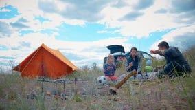 Ouders en jonge geitjes die een picknick hebben en zij gaan nachtelijk in een tent blijven Van reizigersvrouw en kinderen het ont stock video