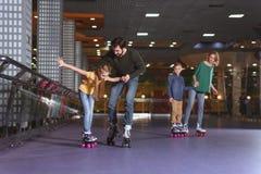 ouders en jonge geitjes die op rol schaatsen stock afbeeldingen