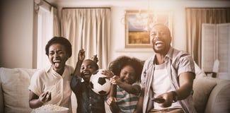 Ouders en jonge geitjes die pret hebben terwijl het letten van op televisie in woonkamer stock foto's
