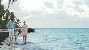 Ouders en kind die langs de strandholding lopen stock videobeelden