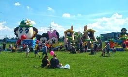 Ouders en kinderen die bij vermaak op een zonnige dag in het park spelen royalty-vrije stock foto