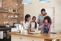 Ouders en Kinderen die Cakes in Keuken samen bakken stock foto's