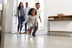 Ouders en Kinderen die Huis terugkeren die Front Door And Running Inside openen royalty-vrije stock foto
