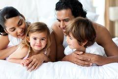 Ouders en kinderen die op het bed liggen Stock Foto's
