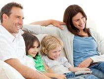 Ouders en kinderen die op televisie samen letten stock afbeelding