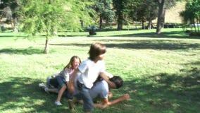 Ouders en kinderen die pret in een park met een bal hebben stock footage