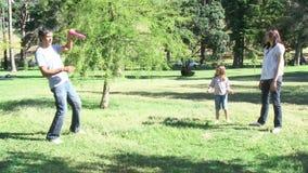 Ouders en kinderen die pret speelhonkbal in een park hebben stock footage