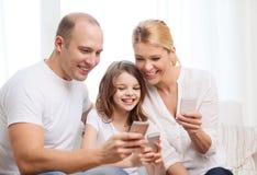 Ouders en meisje met smartphones thuis Stock Foto's