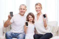 Ouders en meisje met smartphones thuis Stock Afbeeldingen
