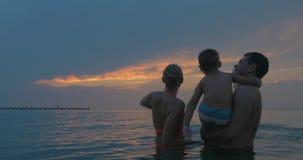 Ouders en zoon die avond van hemel genieten terwijl het baden stock videobeelden