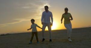 Ouders en Zoon die bij Zonsondergang dansen stock videobeelden