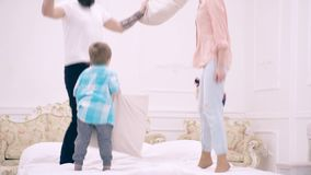 Ouders en zoon die pret met hoofdkussens op bed hebben Familie het besteden vrije tijd thuis Gelukkige familie die op bed samen s stock footage