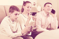 Ouders en zoon die telefoons met behulp van stock foto