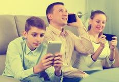 Ouders en zoon die telefoons met behulp van royalty-vrije stock afbeeldingen