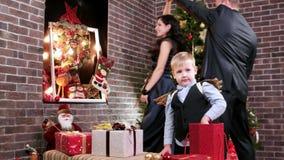 Ouders in het romantische plaatsen, minnaarsouders die, kind het spelen met Kerstmisgiften dichtbij de Kerstboom dansen, stock footage