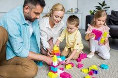 ouders met aanbiddelijke kleine kinderen die met kleurrijke blokken thuis spelen stock foto's