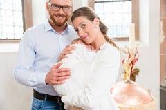 Ouders met baby bij doopsel in kerk stock foto's