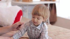 Ouders met een kind die op bed met speelgoed spelen stock video