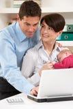 Ouders met het Pasgeboren Werken van de Baby van Huis stock afbeelding
