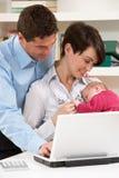 Ouders met het Pasgeboren Werken van de Baby van Huis stock foto's