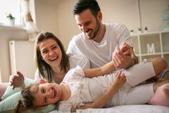 Ouders met hun kleine dochter op bed Stock Fotografie