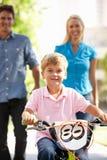 Ouders met jonge jongen op fiets Royalty-vrije Stock Afbeelding