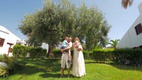 Ouders met kinderen dichtbij olijfboom in groene tuin stock footage