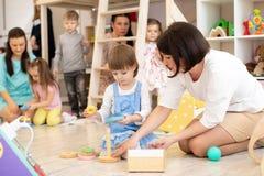 Ouders met kinderen die in speelkamer in opvang spelen royalty-vrije stock fotografie
