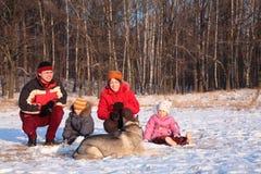 Ouders met kinderen en hond in de winter Stock Afbeelding