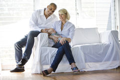 Ouders met slaapbaby op bank in zonnig huis Stock Foto's
