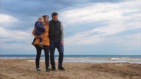 Ouders met weinig dochter die door het overzees op koude dag lopen stock video