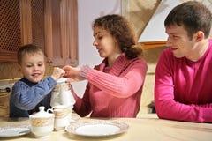 Ouders met zoon bij thee stock afbeeldingen