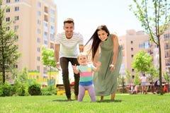 Ouders ondersteunend hun babydochter Stock Foto's