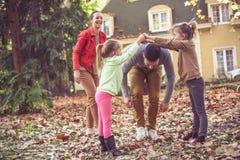 Ouders van het het meisje de speelverstand van de familietijd, de herfstseizoen stock fotografie
