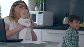 Ouderschap, multitasking mamma die aan tabletcomputer thuis werken met kinderen stock footage