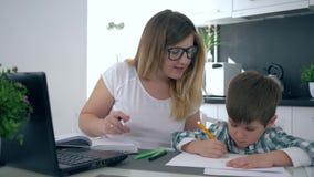 Ouderschap, multitasking mammawerken thuis met zoon bij keuken stock videobeelden