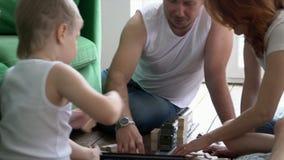 Oudersspel met de zoon De familie speelt houten toren De hechte familie zoekt uit kleine houten blokken a bijeen stock videobeelden