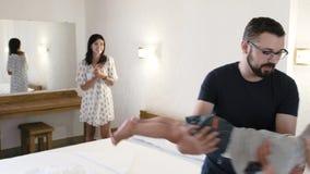 Oudersspel met hun kind in een hotelruimte De vaderrotaties, die zijn zoon in zijn handen houden en zet voorzichtig hem dan stock videobeelden