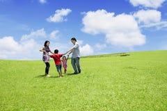 Oudersspelen met hun kinderen in park Stock Afbeeldingen