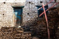 Ouderwetse traditionele vuile houten venster en deur in klein bergdorp in Nepal stock foto's