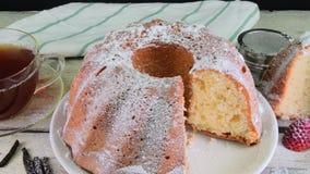 Ouderwetse zandcake met kop van zwarte thee en stukken van vanille op houten achtergrond Dooierbiscuitgebak met stock footage