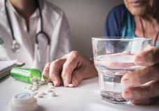 Oudje die dagelijkse medicijndosis thuis nemen stock fotografie