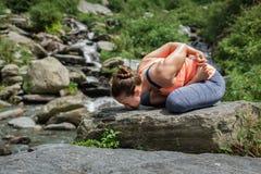 少妇做瑜伽oudoors在瀑布 免版税库存照片