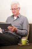 Oudste die aan een tabletPC werkt Stock Afbeelding
