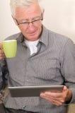 Oudste die aan een tabletPC werkt Stock Afbeeldingen