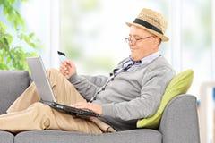 Oudste die aan laptop en een gat makende in creditcard werken Royalty-vrije Stock Afbeelding