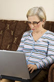 Oudste die aan laptop huis werkt Stock Fotografie