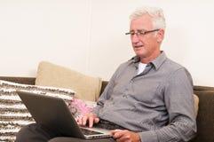 Oudste die aan laptop werkt Royalty-vrije Stock Afbeelding